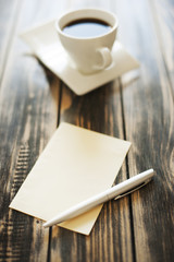 Note, paper, pen and cup of coffee on a wooden table