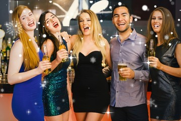 Composite image of laughing friends holding beers posing