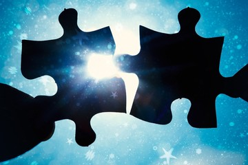 Composite image of hand holding two jigsaw pieces