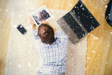 Woman lying on the floor using her tablet and notebook