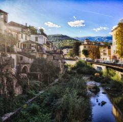 Italienisches Dorf mit Fluß und Brücke