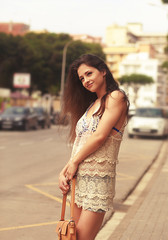 Beautiful woman standing near road on the street background