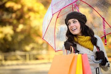 Happy woman with shopping bags in autumn