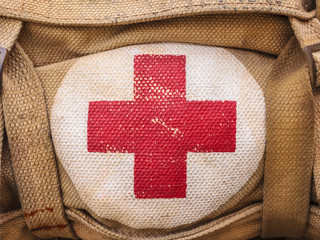 Red cross medical aid symbol on an old army bag