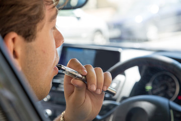 Man smoking an e-cigarette as he drives a car