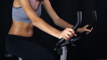 Close up of a young woman riding stationary bike