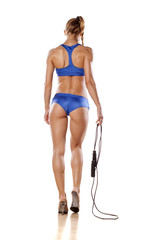 pretty muscular woman goes with jumping rope
