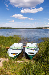 Lake scenery with two wooden boat in summertime
