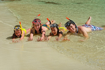 Happy family in snorkels on beach having fun on vacation