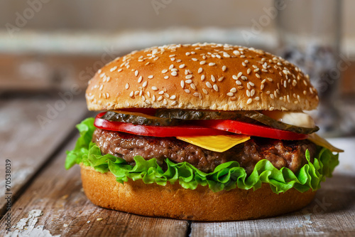 hamburger with cutlet grilled on a wooden surface - 70538039