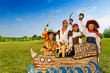 Four kids in pirate costumes behind ship - 70539269