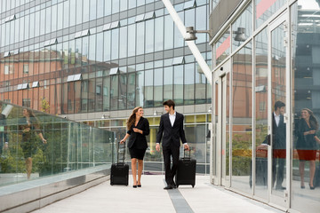 Young business couple walking with suitcase