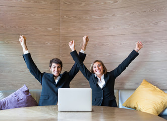 Young business couple celebrating in front of computer