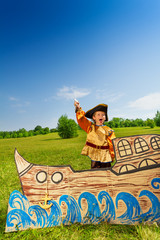 Excited boy in pirate costume laughing on ship