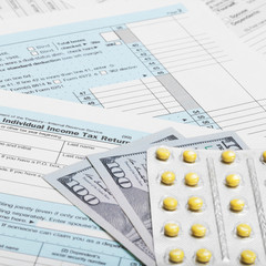 US Tax Form 1040 with 100 dollars and pills - 1 to 1 ratio