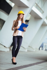 A pretty young woman working as architect on a construction site