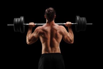 Studio shot of a bodybuilder lifting a barbell