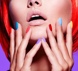 Women hands with bright multicolor nails near face