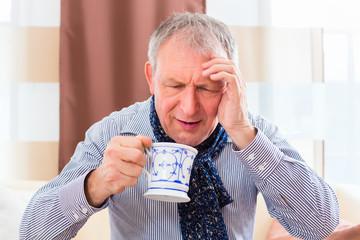 Senior trinkt Tee und kuriert Erkältung