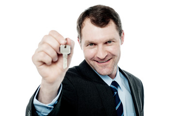 Happy businessman holding a house key