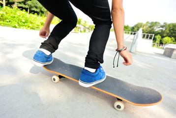 skateboarding woman legs jump at skatepark