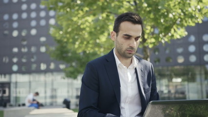 Young businessman sitting in a park near office and using laptop