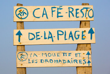 Welcome cafe sign on the beach with blue sky
