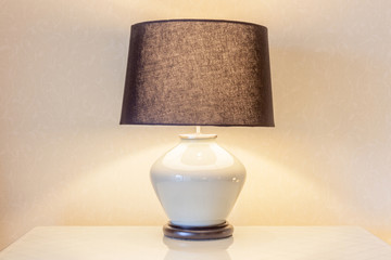 Table lamp and its shadow on wallpaper in the bedroom