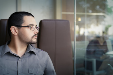 Young Man Wearing Glasses Looking Out of a Window