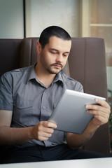 Young Man looking at His Tablet