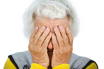 Depressed old woman covering face with wrinkled hands
