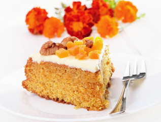 Piece of carrot cake with icing on white plate