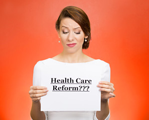 Skeptical woman holding Health care reform? sign