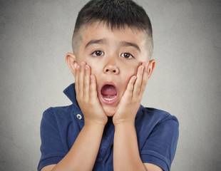 Child with astonished face expression on grey wall background