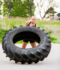 Fit Woman Flipping Tire Outdoors