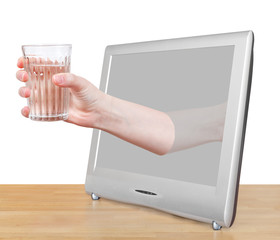hand holding natural water in glass leans out TV