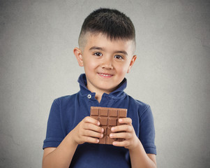 Boy eating whole bar of chocolate isolated on grey background