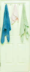 Blue, Pink and Green towel hang on a wooden door.