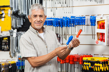 Happy Customer Comparing Screwdrivers In Hardware Shop