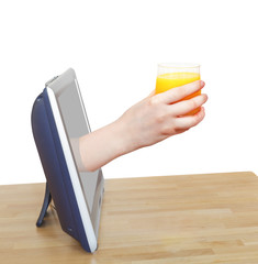 glass with fresh orange juice in hand leans out TV