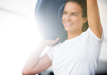 Woman Lifting Barbell Plate in Box