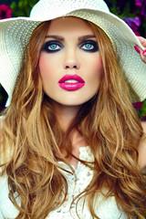 beautiful sexy blond model in hat near summer flowers