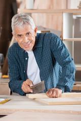 Senior Man Cutting Wood With Saw In Workshop