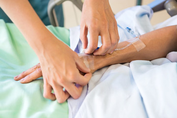 Female Nurse Attaching IV Drip On Male Patient's Hand