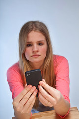 Scandinavian cute young girl looking irritated at her phone