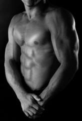 Sexy muscular man in shades of grey on dark background
