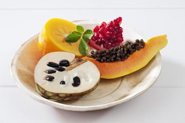 Exotische Früchte im Teller auf weissem Untergrund