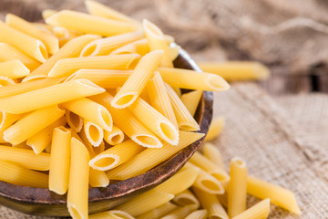 Raw Penne on wooden background