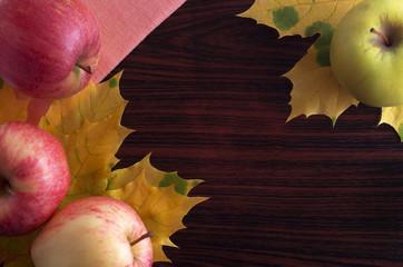 Яблоки и опавшие листья на деревянном столе
