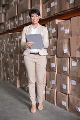 Pretty warehouse manager smiling at camera